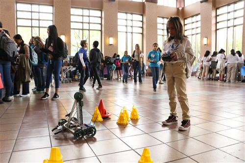 Young Ysleta ISD student controls a robot with remote control.