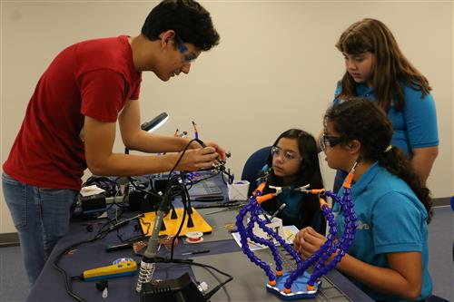 El Paso Electric employee shows three young students how to do soldering.